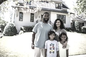 A family poses in front of a house