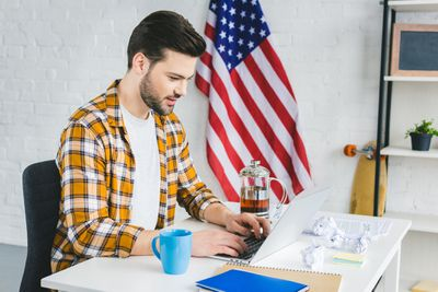 Man working on laptop with U.S. flag in the background