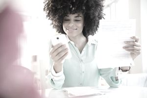 woman holding up a bill and looking at smartphone