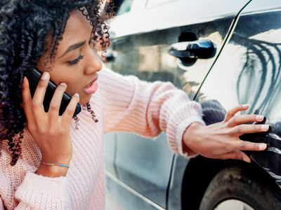 Woman examining scratches on her car while on the phone