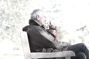 Smiling senior couple hugging on a park bench