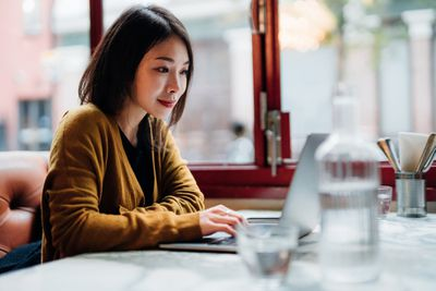 A woman checks her investment fund on her laptop while sitting in a cafe