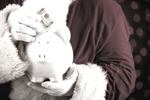 Person in a Santa suit putting money into a piggy bank