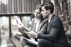 Male and female professionals studying paperwork together, the woman pointing at something in a document