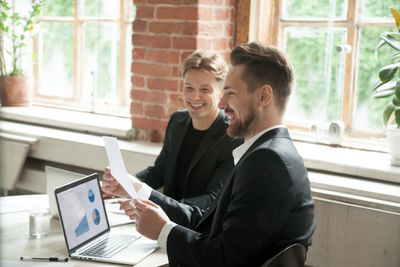 Two executives happily reviewing company growth numbers