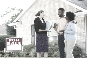A couple talking with a real estate agent.