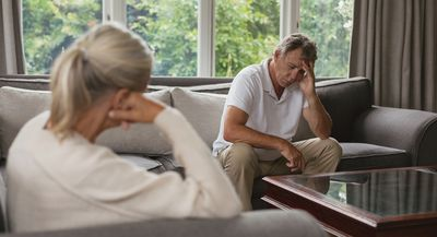 Senior man sits with hand on forehead on couch in comfortable home