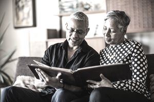 Retired couple looking at photo album on a couch at home