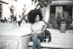 Young woman in striped top looks at her phone with a credit card in hand on outdoor bench.