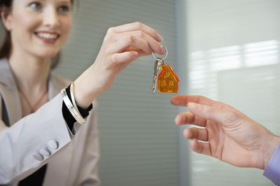 woman handing house keys to another person