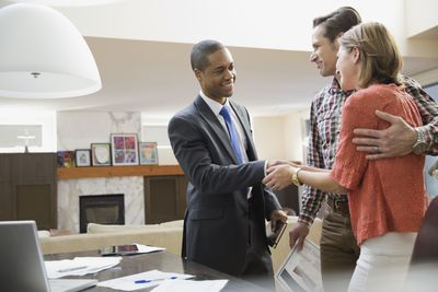 Couple shaking hands with their accountant.