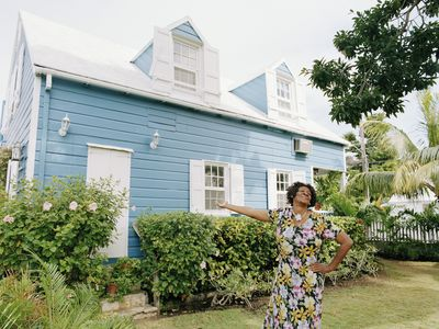 A woman in a floral dress proudly gestures toward her bright blue house with white shutters and a lovely garden