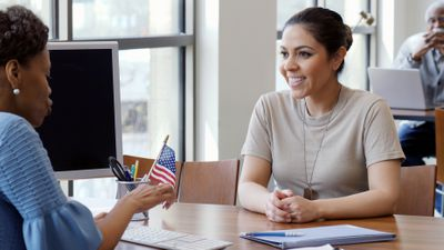 Smiling female soldier talks with bank loan officer