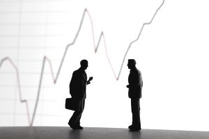 silhouette of two men in front of giant line graph
