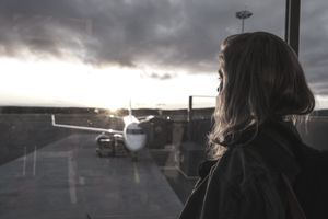 person looking out the window at an airplane on the runway during sunset