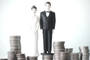 Bride and groom cake toppers standing on stacks of coins