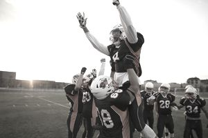 Teenage boy high school football players lifting celebrating, cheering teammate on football field