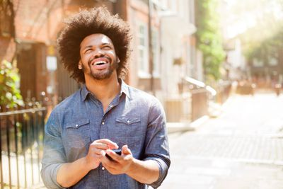 A man smiles while using his phone.