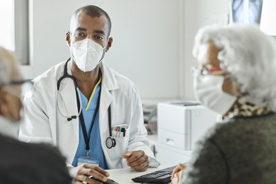 Doctor discussing with couple during COVID-19.