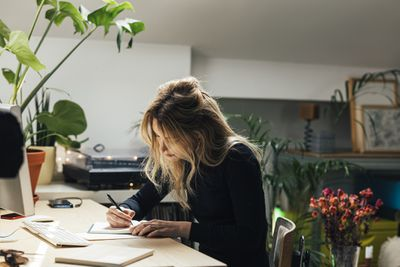 Young woman writes on notepad in home office