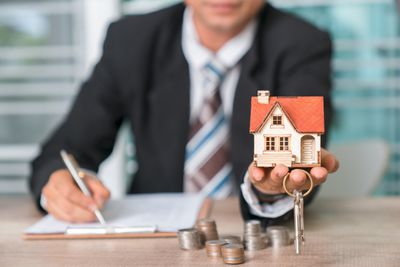 man in a suit and tie filling out paperwork holding a house figurine and house keys with pile of change on the table