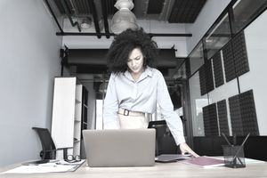 A standing woman in business attire looks at a computer screen.