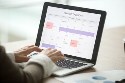 Person updating calendar on laptop.