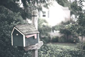 House shaped mailbox on a post with a home in the background.