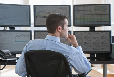 Day trader working with multiple computer screens in front of him