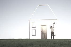 Man constructing a wooden image of a house against a blue sky