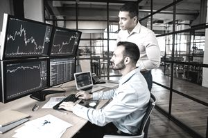 Two traders checking screens.