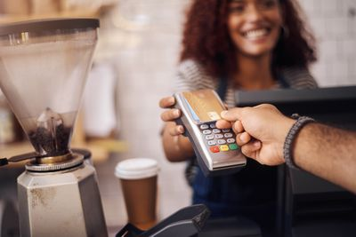 Employee makes credit card touch transaction at a store