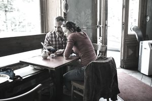 Couple in Cafe reading Tour Guide
