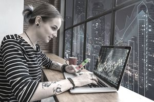 Woman using laptop to trade currency