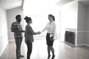 Young couple looking at a new house with a real estate agent