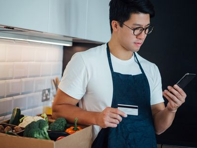A man in an apron holds a credit card and a phone.