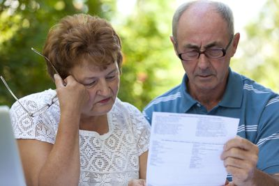 Unhappy man and woman read a past-due notice on a cosigned loan