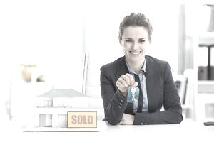 women with key and a sold sign