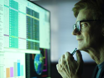 Man working in an office, studying a large computer monitor displaying a variety of numerical data, global information and text.