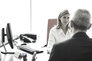 A woman behind a desk smiles wryly at a man sitting opposite her.