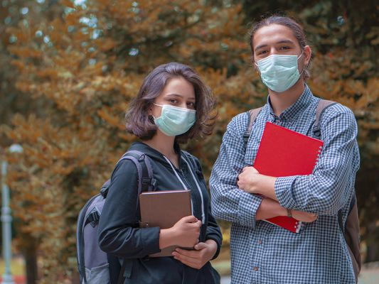 Two masked students are chatting in a campus. - stock photo