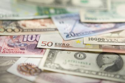 An assortment of foreign currencies spread out on a surface