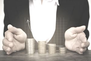 Digital Composite Image Of Businessman Covering Stacked Coins With Line Graph