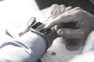 man looking at smart watch with financial paperwork on desk
