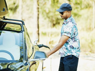 A man in sunglasses and a bright hawaiian shirt charges his electric car