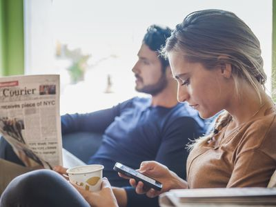 couple with newspaper and cell phone in coffee shop