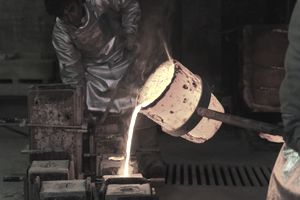 foundry worker pouring hot metal into cast mold