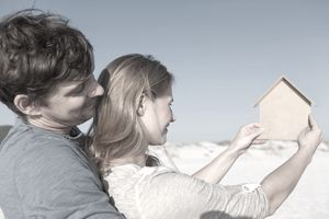 Couple planning for a future beach home standing on the beach looking at a cardboard cut out of a house.