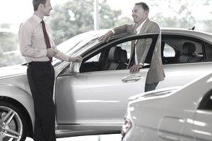 Salesman talking to man in automobile showroom