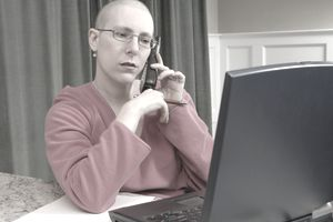 A chemotherapy patient worried over medical bills talks on phone while sitting in front of an open laptop